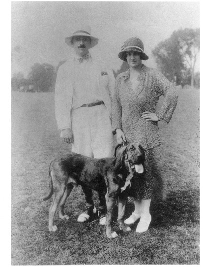 Full-length photograph of Alfred A. and Blanche Knopf posed outside with a dog.