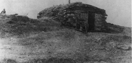 Photograph of a dugout, facing the front door, build into a rise.