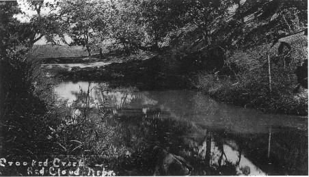 """Photograph of a creek, with a handwritten caption in white at the bottom, which reads """"Crooked Creek Red Cloud Nebr."""""""