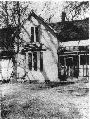 Photograph of the Garber house from the side, showing the kitchen door and another bay window.