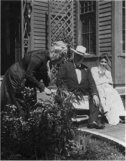 Photograph of Charles Perkins and his daughter Alice sitting on the porch of a house, while Edith Forbes Perkins picks flowers in the garden next to them.