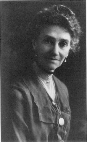 Bust-length studio portrait of Lyra Wheeler Garber, looking dorectly into the camera. wearing dangling earrings, a long necklas, and a high-necked dress.