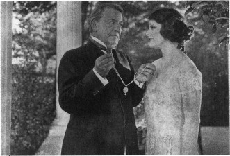George Fawcett presenting Irene Rich with a necklace, in their roles as MArian and Daniel Forrester in the 1925 film adaptation of A Lost Lady.