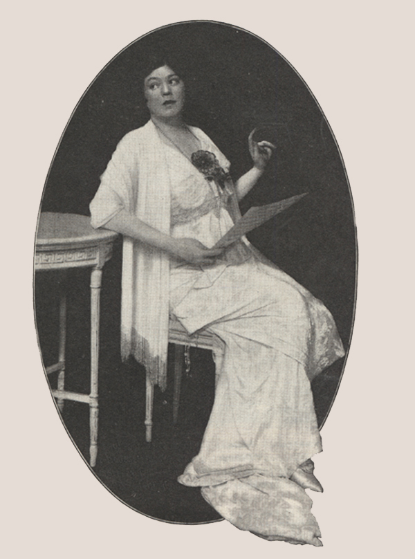 Ethel Barrymore sitting on a chair and holding a sheet of music.