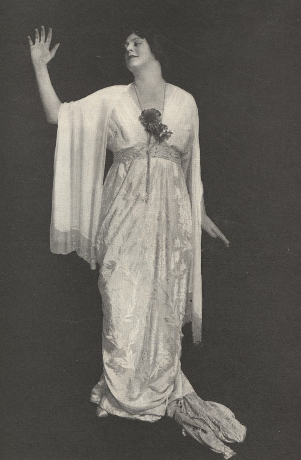 A full-length photograph of Barrymore as Tante, her right hand raised and her head turned to the side.