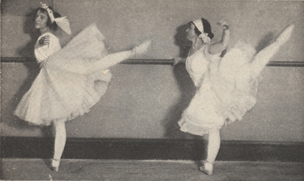 Two female ballet dancers at the bar, standing on one toe with other leg lifted behind them.