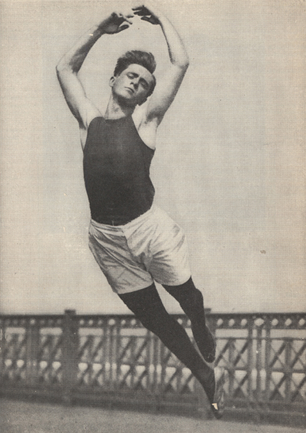 Male ballet dancer in the air, several feet off of the ground, with arms forming a circle around his head.