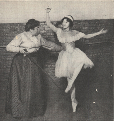 Female ballet dancer with her instructor, who is holding a stick.