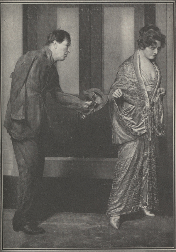 Photograph of woman in elegant costumestanding with her back to the actor portraying the one-armed tramp who is tugging at her sleeve.
